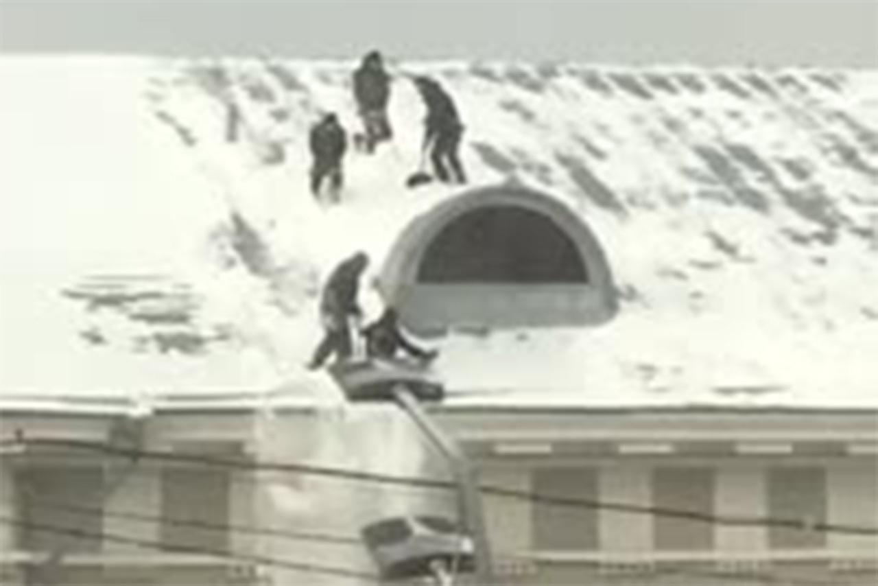 Скатывающиеся с крыши во время уборки снега дворники в Москве попали на видео